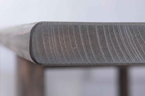 Nahaufnahme der Holzmaserung an der abgerundeten Bohle der Tischplatte am Tisch Maikrabats