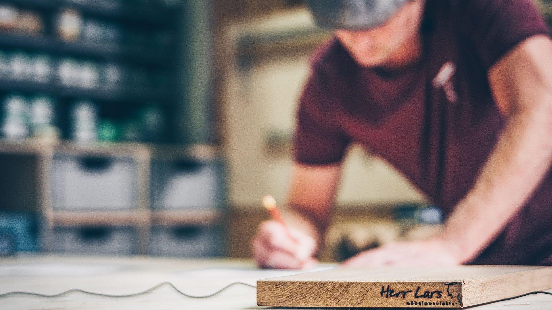 Lars schreibt eine Karte an einen Kunden