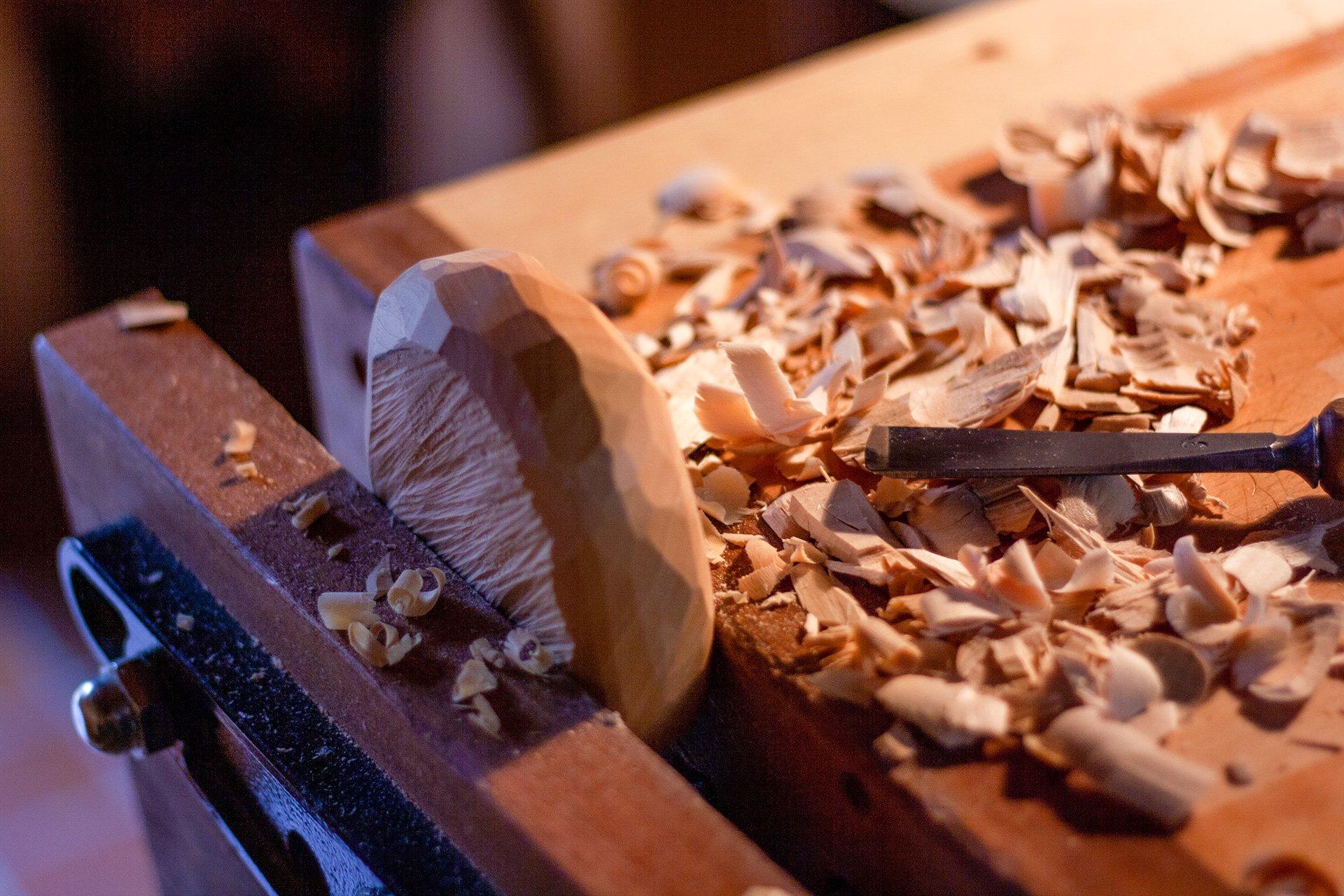 Fertigung einer DIPFELE Servierschale in der Werkstatt mithilfe eines traditionellen Schnitzmessers.
